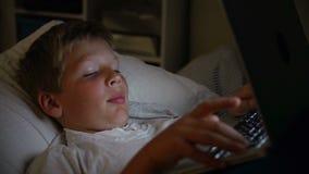 Αγόρι που χρησιμοποιεί το φορητό προσωπικό υπολογιστή στο κρεβάτι τη νύχτα απόθεμα βίντεο