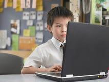 Αγόρι που χρησιμοποιεί το lap-top στην τάξη στοκ εικόνα με δικαίωμα ελεύθερης χρήσης