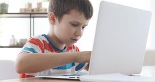 Αγόρι που χρησιμοποιεί το lap-top στο σπίτι απόθεμα βίντεο