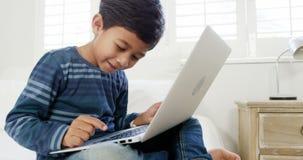 Αγόρι που χρησιμοποιεί το lap-top χαλαρώνοντας στο κρεβάτι φιλμ μικρού μήκους