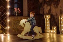 Αγόρι σε ένα άλογο λικνίσματος Στοκ Εικόνες
