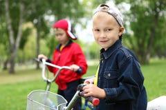 Αγόρι σε ένα ποδήλατο στο πράσινο πάρκο Στοκ Εικόνες