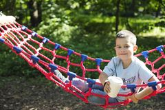 Αγόρι σε μια αιώρα με ένα φλυτζάνι εγγράφου του ποτού στοκ φωτογραφία