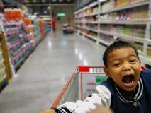 Αγόρι σε Supermaket Συνεδρίαση αγοριών στο κάρρο αγορών στοκ φωτογραφία με δικαίωμα ελεύθερης χρήσης