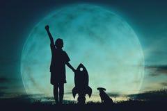 Αγόρι σκιαγραφιών που κρατά ένα έγγραφο πυραύλων και που παίζει με λίγο σκυλί Στοκ εικόνες με δικαίωμα ελεύθερης χρήσης
