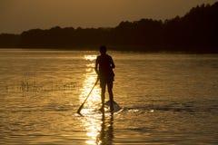 Αγόρι σκιαγραφιών στη στάση γουλιά-πινάκων επάνω στον πίνακα κουπιών αργά το βράδυ κατά τη διάρκεια του ηλιοβασιλέματος Στοκ Εικόνες