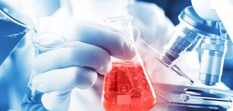 Αγόρι σπουδαστών φαρμακοποιών που χύνει το μπλε υγρό στο γυαλί beger erlenmeyer στη χημεία φιαλών με το κόκκινο υγρό στο βιοχημικ στοκ φωτογραφία με δικαίωμα ελεύθερης χρήσης