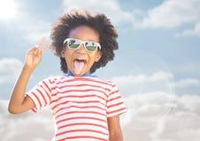 Αγόρι στα γυαλιά ηλίου που κάνει το σημάδι ειρήνης ενάντια στον ουρανό με τη φλόγα Στοκ φωτογραφία με δικαίωμα ελεύθερης χρήσης