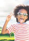 Αγόρι στα γυαλιά ηλίου που κάνει το σημάδι ειρήνης ενάντια στους τομείς με τη φλόγα Στοκ εικόνα με δικαίωμα ελεύθερης χρήσης
