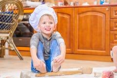 Αγόρι στα καπέλα αρχιμαγείρων ` s κοντά στη συνεδρίαση εστιών στο πάτωμα κουζινών που λερώνεται με το αλεύρι, παίζοντας με τα τρό Στοκ φωτογραφία με δικαίωμα ελεύθερης χρήσης