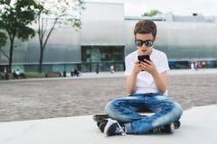 Αγόρι στην άσπρη μπλούζα και κάθισμα γυαλιών ηλίου υπαίθριο στο longboard και το smartphone χρήσεων Το αγόρι παίζει τα παιχνίδια  Στοκ φωτογραφία με δικαίωμα ελεύθερης χρήσης
