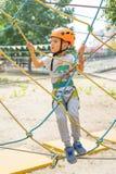 Αγόρι στην αναρρίχηση της δραστηριότητας στο υψηλό δασικό πάρκο καλωδίων Cableway επιτραπέζιων βουνών παιδιά ειδικά πάλι Στοκ φωτογραφία με δικαίωμα ελεύθερης χρήσης