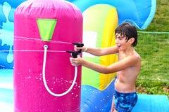 Αγόρι στην ολίσθηση κολύμβησης στον ψεκασμό νερού aquapark Στοκ Εικόνες