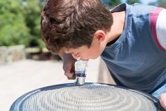 Αγόρι στην πηγή νερού που απολαμβάνει ένα δροσερό ποτό Στοκ εικόνα με δικαίωμα ελεύθερης χρήσης