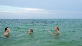 Αγόρι στη θάλασσα που περπατά από τη μητέρα στον πατέρα απόθεμα βίντεο