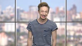 Αγόρι στη ριγωτή μπλούζα που γελά σκληρά φιλμ μικρού μήκους