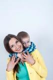 Αγόρι στη συνεδρίαση πουκάμισων με το mom στο ελαφρύ υπόβαθρο Στοκ φωτογραφία με δικαίωμα ελεύθερης χρήσης