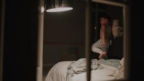 Αγόρι στις πυτζάμες που πηδά στο κρεβάτι στην κρεβατοκάμαρα του σπιτιού του Παιχνίδια γέλιου με ένα παιχνίδι φιλμ μικρού μήκους