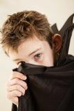 Αγόρι στον επενδύτη βαμπίρ που καλύπτει μέρος του προσώπου Στοκ Εικόνα