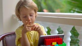 Αγόρι στους τροπικούς κύκλους που μιλούν με τους φίλους και την οικογένεια στην τηλεοπτική κλήση που χρησιμοποιεί μια ταμπλέτα κα φιλμ μικρού μήκους