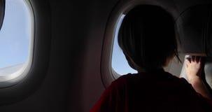 Αγόρι στο κάθισμα που φαίνεται έξω ένα παράθυρο αεροπλάνων φιλμ μικρού μήκους