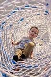 Αγόρι στο καθαρό μανίκι του λούνα παρκ που αναρριχείται στη δυνατότητα Στοκ Εικόνες