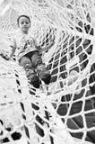Αγόρι στο καθαρό μανίκι του λούνα παρκ που αναρριχείται στη δυνατότητα Στοκ φωτογραφία με δικαίωμα ελεύθερης χρήσης