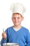 Αγόρι στο καπέλο του αρχιμάγειρα με την κουτάλα και το τηγάνι Στοκ Φωτογραφίες