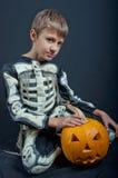 Αγόρι στο κοστούμι αποκριών με την πορτοκαλιά κολοκύθα Στοκ Φωτογραφίες