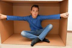 Αγόρι στο κουτί από χαρτόνι στοκ φωτογραφία