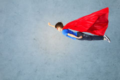 Αγόρι στο κόκκινο ακρωτήριο superhero και μάσκα που πετά στον αέρα Στοκ Φωτογραφία