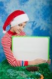 Αγόρι στο κόκκινο καπέλο Santa που κρατά το λευκό πίνακα Στοκ φωτογραφίες με δικαίωμα ελεύθερης χρήσης