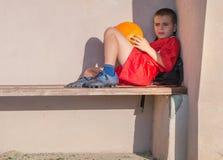 Αγόρι στο κόκκινο ποδόσφαιρο Τζέρσεϋ που κάθεται σε έναν πάγκο Στοκ φωτογραφίες με δικαίωμα ελεύθερης χρήσης
