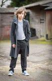 Αγόρι στο μακρύ παλτό που στέκεται σε ένα αγροτικό ναυπηγείο στοκ εικόνες