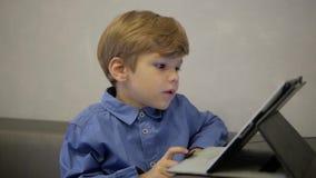 Αγόρι στο μπλε πουκάμισο που λειτουργεί στην ταμπλέτα Επιχείρηση απόθεμα βίντεο