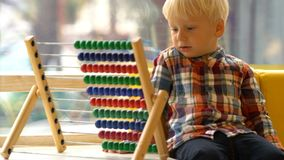 Αγόρι στο παιχνίδι παιδικών σταθμών με τον άβακα φιλμ μικρού μήκους