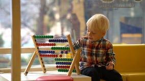 Αγόρι στο παιχνίδι παιδικών σταθμών με τον άβακα απόθεμα βίντεο