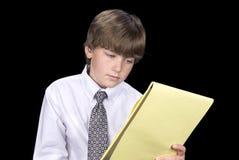 Αγόρι στο σημειωματάριο ανάγνωσης επιχειρησιακών φορεμάτων στοκ εικόνα με δικαίωμα ελεύθερης χρήσης