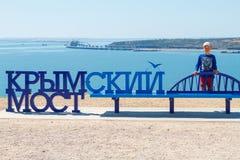 Αγόρι στο υπόβαθρο της θάλασσας κοντά στην της Κριμαίας γέφυρα επιγραφής στοκ φωτογραφία με δικαίωμα ελεύθερης χρήσης