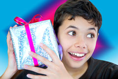Αγόρι συγκινημένο κράτημα ενός τυλιγμένου επάνω χριστουγεννιάτικου δώρου Στοκ Εικόνες