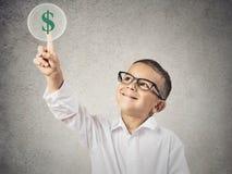 Αγόρι σχετικά με το πράσινο σημάδι δολαρίων στοκ φωτογραφίες