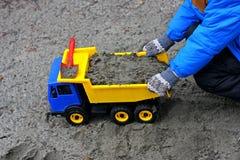 Αγόρι, το οποίο φορτώνει το αυτοκίνητο παιχνιδιών άμμου στοκ φωτογραφία με δικαίωμα ελεύθερης χρήσης