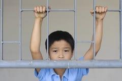 Αγόρι λυπημένο πίσω από τα σιδερόβεργα Στοκ Φωτογραφίες