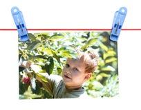 Αγόρι φωτογραφιών σε ένα σχοινί με ένα clothespin σε ένα άσπρο υπόβαθρο Στοκ Εικόνα