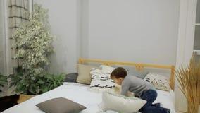 Αγόρι 5-7 χρονών στο τζιν παντελόνι και μια γκρίζα ευρωπαϊκή εμφάνιση πουλόβερ που πηδά ευτυχώς στο κρεβάτι στους γονείς απόθεμα βίντεο