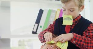 Αγόρι ως ανώτατο στέλεχος επιχείρησης που τοποθετεί τις κολλώδεις σημειώσεις πέρα από τα μάτια συναδέλφων 4k φιλμ μικρού μήκους