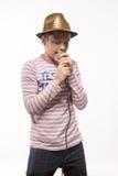 Αγόρι brunette τραγουδιστών σε έναν ρόδινο άλτη με ένα μικρόφωνο και τα ακουστικά Στοκ Εικόνα