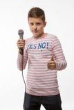Αγόρι brunette τραγουδιστών σε έναν ρόδινο άλτη με ένα μικρόφωνο Στοκ Φωτογραφία