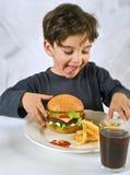 αγόρι chessburger που τρώει τις νεο στοκ εικόνες