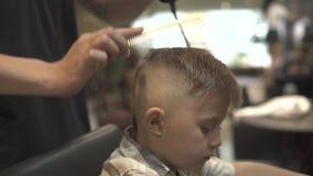 Αγόρι hairstyle με το στεγνωτήρα στο barbershop Ξήρανση τρίχας παιδιών στο σαλόνι κουρέων Ορίζοντας μικρό παιδί τρίχας κομμωτών μ απόθεμα βίντεο